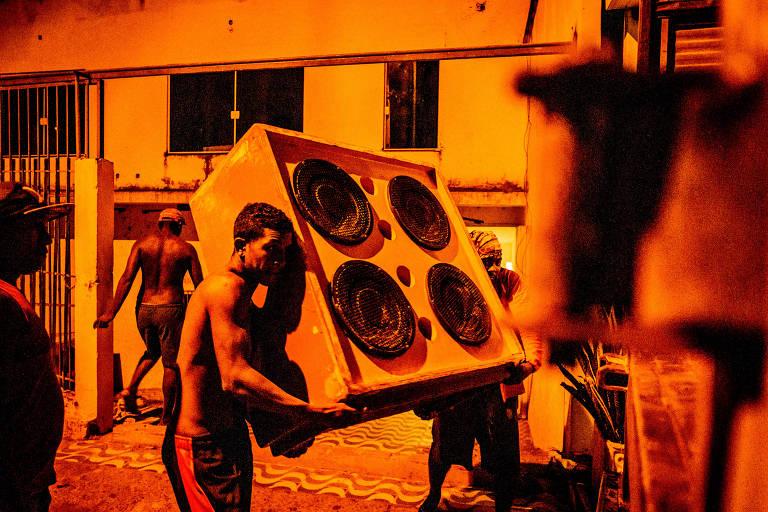 Homens carregam caixa de som para festa de reggae em São Luís