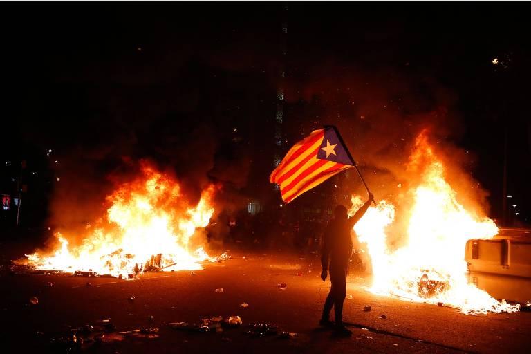 Latas de lixo em chamas do lado de fora do Camp Nou, onde manifestantes entraram em confronto com a polícia