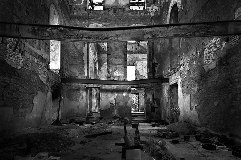 A sala de exposição está em ruínas, totalmente escura e abandonada. As paredes estão queimadas e há entulhos e escombros espalhados pelo chão.