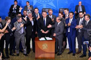 Parlamentares fazem o svåmbolo da arma com os dedos ao lado de Bolsonaro