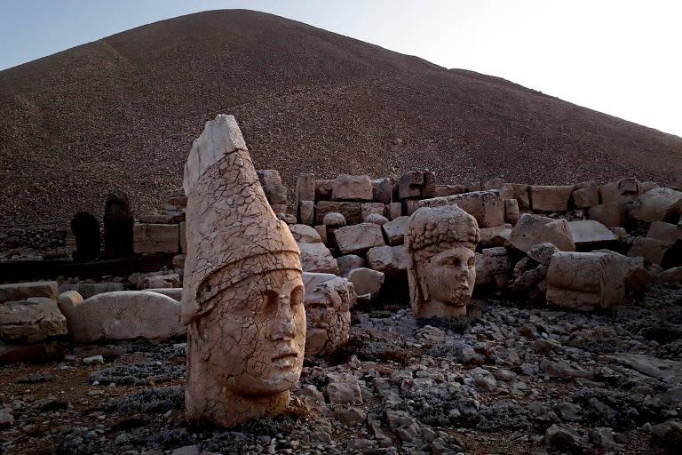 Esculturas no monte Nemrut; a elevação ao fundo, construída com pequenas pedras, é o mausoléu do rei Antíoco de Comagena, representado na estátua da esquerda