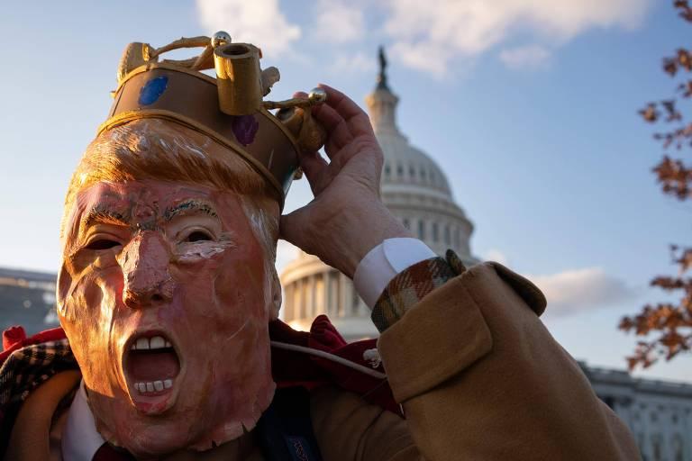 Manifestante contrário a Trump protesta enquanto parlamentares debatem artigos do impeachment, em Washington