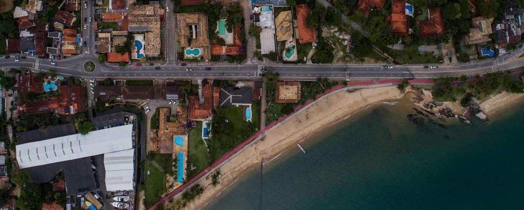 Vista aérea de bairro litorâneo com mar e faixa de areia abaixo à direita, avenida ao centro e telhados de casas