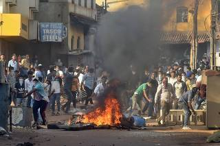 Demonstrators throw stones towards police during a protest against a new citizenship law, in Mangaluru