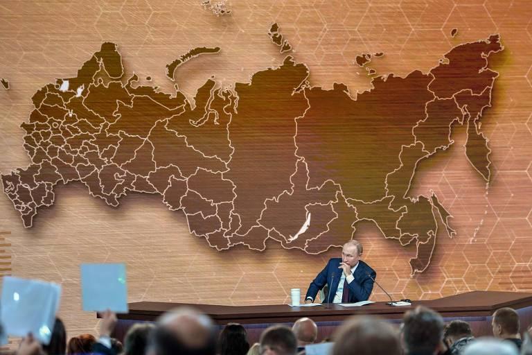 Com jornalistas mostrando cartazes para pedir a palavra, Putin ouve questão em entrevista