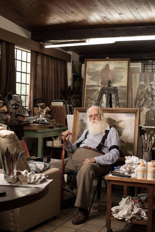 Homem velho sentado com bengala em meio a quadros