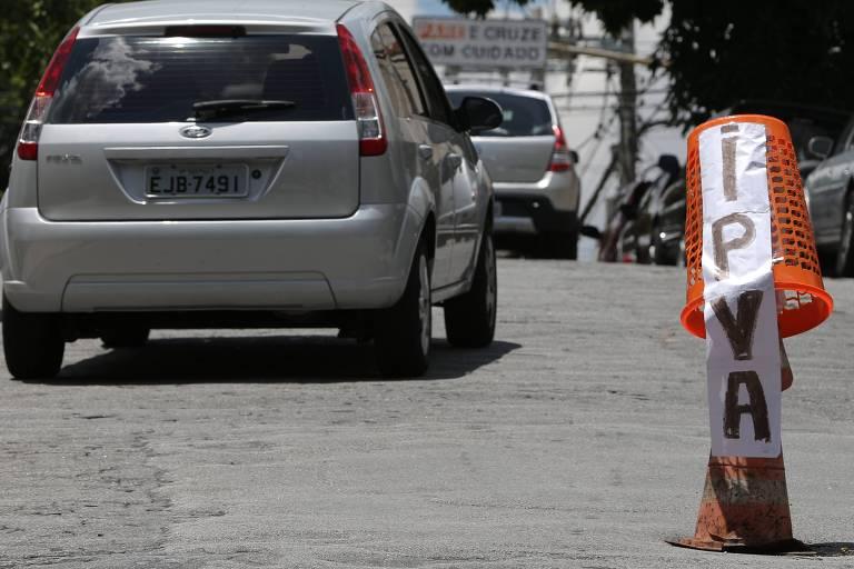 Carro passa em rua onde cone foi colocado em buraco com um cartaz escrito IPVA