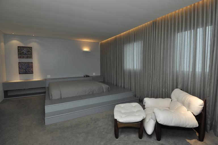 No quarto projetado pela arquiteta Nara Grossi, da Gema Arquitetura, o tom cinza domina o ambiente e contrata com a poltrona branca e a luminária Abatjour de Arte