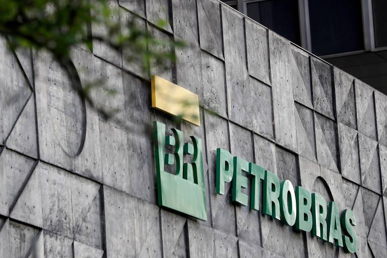 O logo da Petrobras aparece na sede da companhia no Rio de Janeiro. O logo, escrito em verde, está em uma parede cinza. Em primeiro plano, desfocada, está a copa de uma árvore