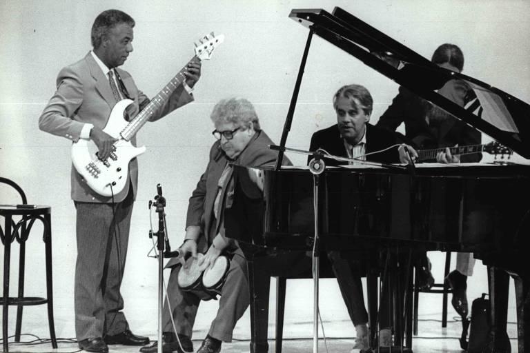 Jô Soares, sentado em um piano, junto aos integrantes do sexteto de músicos que o acompanhava no programa. Bira, de terno, está em pé e toca um baixo branco.