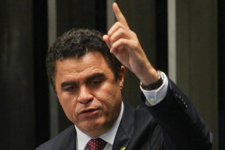 O senador está de terno e gravata e discursa gesticulando com as mãos; ele aponta para o alto