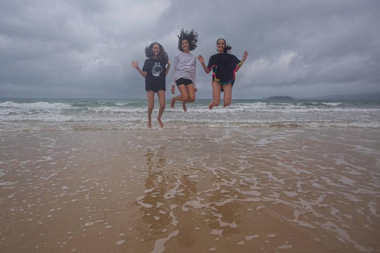 Três meninas dão um salto no ar na beira de uma praia com o mar bem calmo. Elas estão de camiseta e short