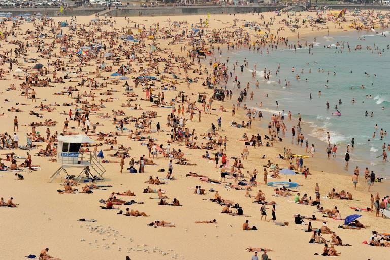 Dezenas de banhistas na areia e alguns no mar