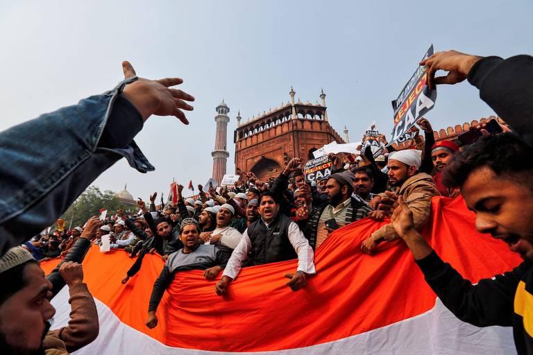Manifestantes com a bandeira da Índia protestam em frente à mesquita de Jama Masjid, em Déli, contra a nova lei de cidadania