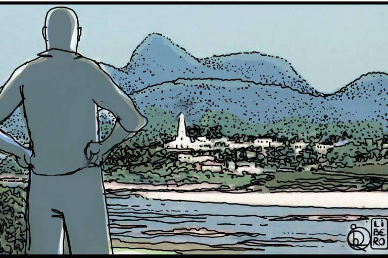 Um homem com os braços na cintura olha uma paisagem com montanhas, vegetação e água