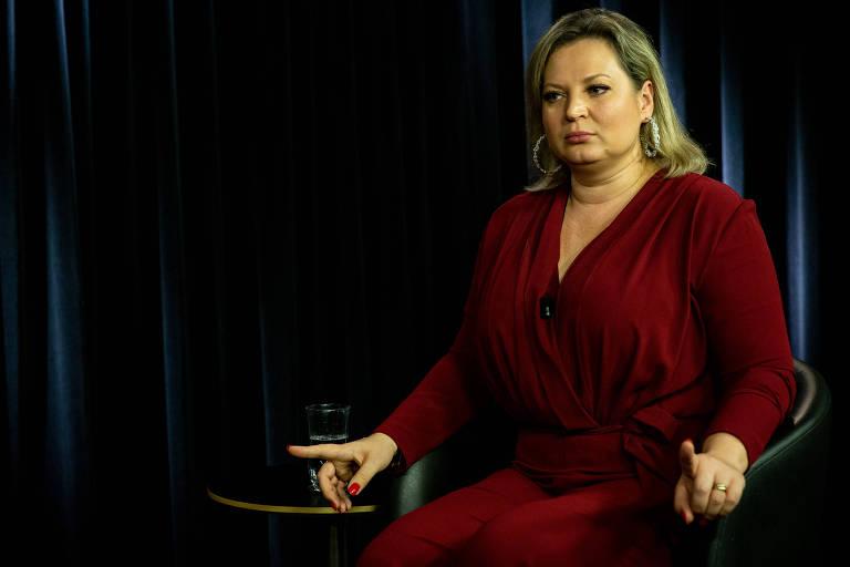 Mulher sentada usa vestido vermelho com rosto sério