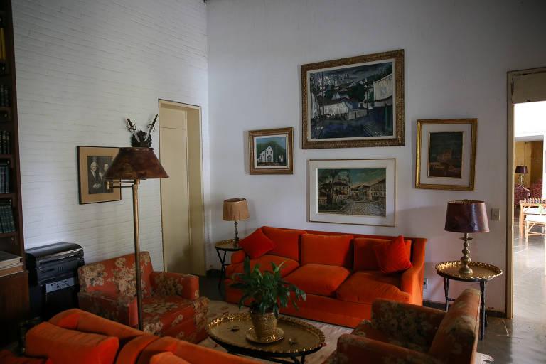 Sofás vermelhos em sala antiga, com quadros nas paredes, tapete, mesa e centro e vários objetos sobre elas