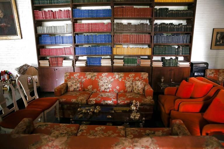 Prateleira repleta de livros; sofás laranjas e florais compõem o ambiente