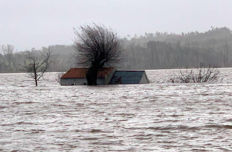 Única casa é vista, com água na altura do telhado