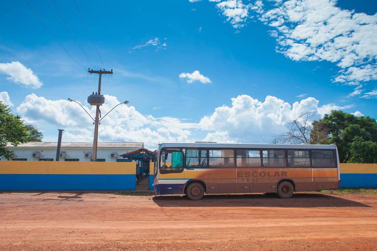 Ônibus escolar parado em chão de terra batida diante de muro de escola