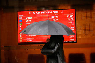 FILE PHOTO: A person carrying an umbrella walks past an electronic board showing currency exchange rates, in Buenos Aires