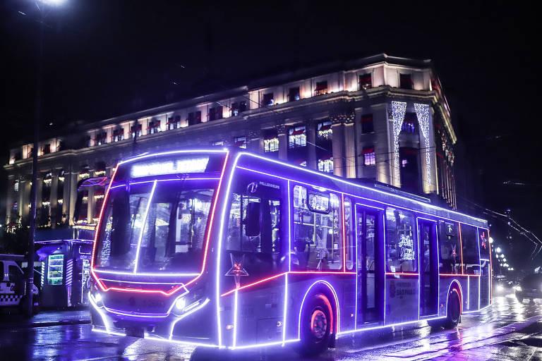 Imagem mostra ônibus iluminado nas laterais com linhas de luzes roxas e brancas, passando por rua durante a noite