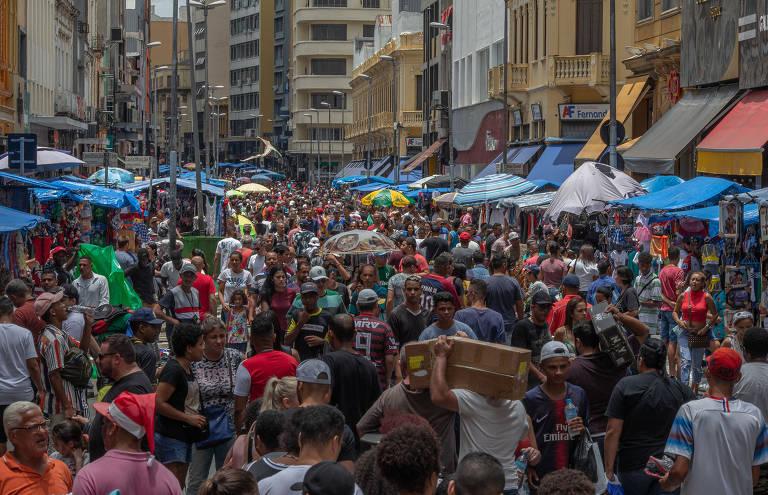 Uma multidão toma a rua toda, de calçada a calçada, ao menos dois quarteirões. As pessoas carregam pacotes, caixas e sacolas, e há guarda-sóis no meio da massa de gente, de vendedores ambulantes