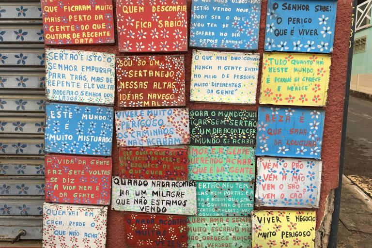 Imagem mostra peças retangulares, presas em uma parede vermelha, com frases de Guimarães Rosas