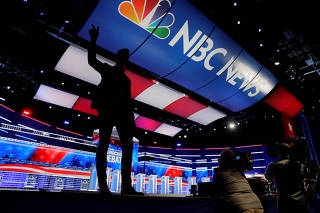 An NBC employee talks to members of the media in front of the stage and podiums to be used for the next U.S. Democratic presidential candidates debate in Atlanta