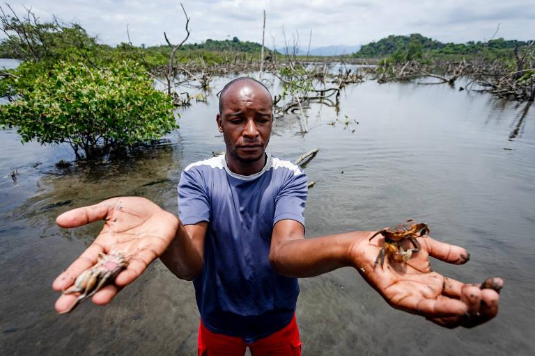 Rafael Santos Pereira mostra o que conseguiu pegar; óleo se espalhou por 23 praias e atingiu a área de preservação ambiental de Guapimirim, a maior área de mangue preservado no estado do Rio