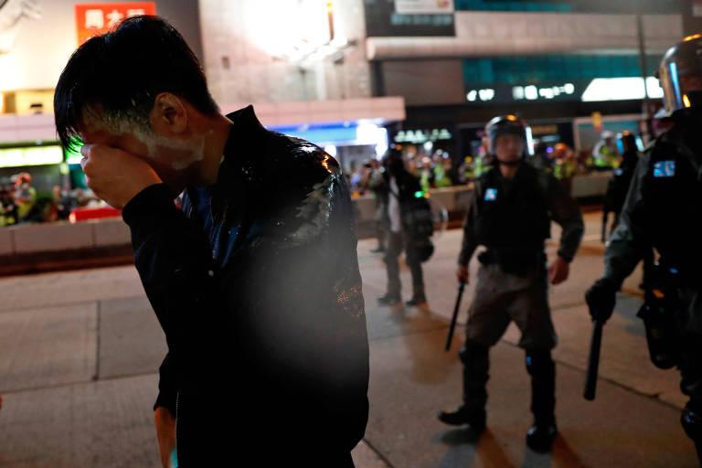 Homem é atingido por spray de pimenta jogado pela polícia durante protesto antigoverno no dia de Natal em Hong Kong