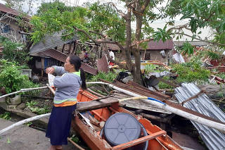 A woman is seen near storm debris in Biliran