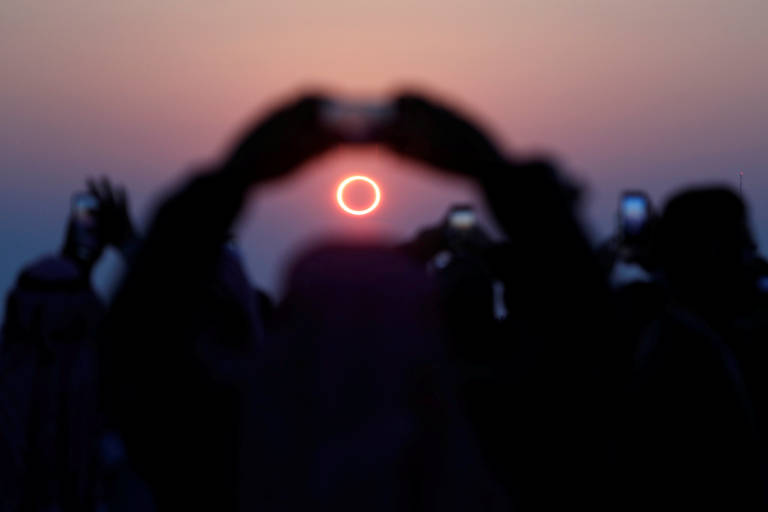 Imagem mostra sombra de pessoas tirando foto de eclipse . No céu ao fundo, é possível ver um anel vermelho completo, formado pelo fenômeno