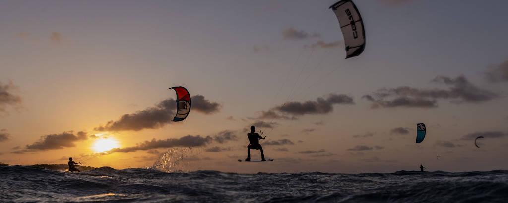 Pessoas estão no mar, durante o entardecer, praticando kitesurf; eles parecem voar sobre a água