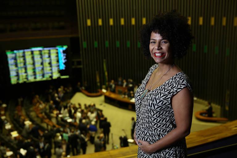 Áurea, uma mulher negra, com as mãos sobre a barriga de gestante. Ao fundo, o plenário da Câmara