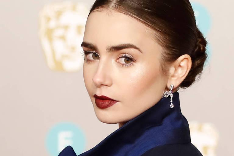 Pele iluminada é a aposta da make de Lily Collins combinada ao batom vermelho