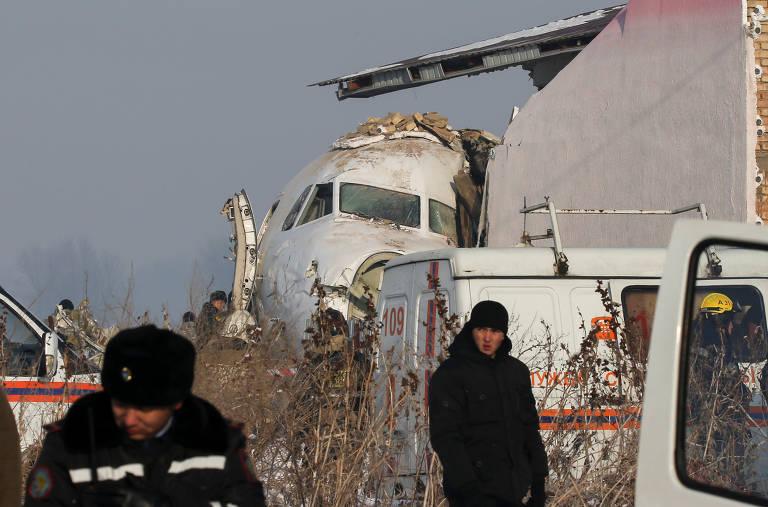 Na imagem é possível ver uma parte das ferragens de um avião branco, com algumas pessoas com roupas de frio em volta, em meio a uma planície aberta coberta de neve e plantes secas