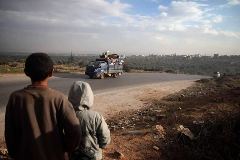 Duas crianças de costas na beira da estrada observam pequeno caminhão de suprimentos passar