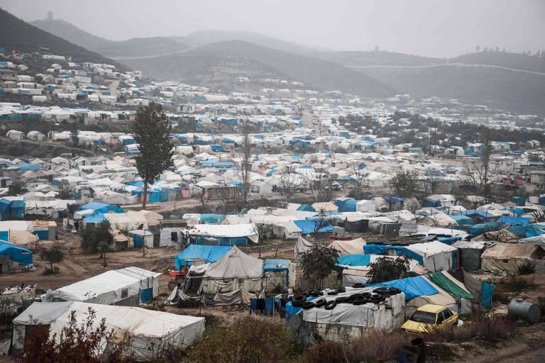 Dezenas de tendas brancas e azuis, espalhadas em um campo. Ao fundo, montanhas com névoa