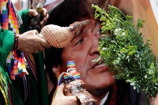 Peruvian shamans hold a poster of former Bolivian President Evo Morales as they perform a ritual of predictions for the new year at Pescadores beach in Chorrillos, Lima