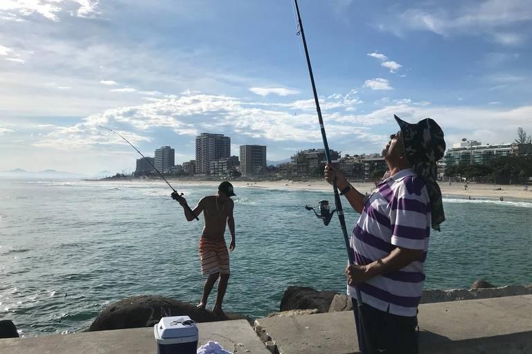 Mulher de blusa listrada pesca diante de uma mureta; adiante, jovem entra no mar