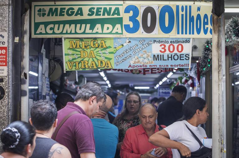 Aglomeração de pessoas diante de porta com dizeres MEGA SENA ACUMULADA