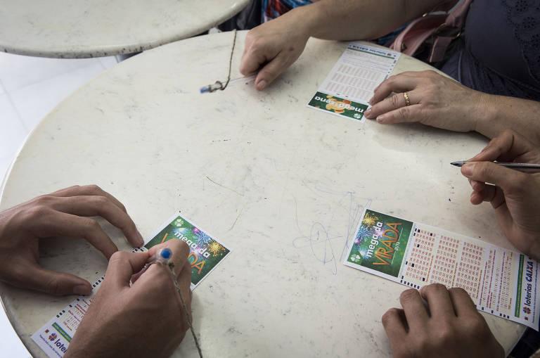 Mesa com cartelas de loteria e as mãos dos apostadores que as preenchem