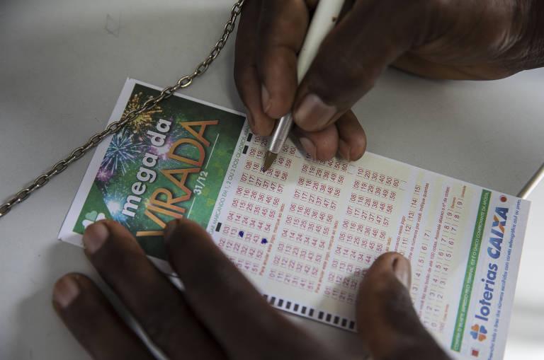 Mãos de pessoa negra preenchem cartela de loteria
