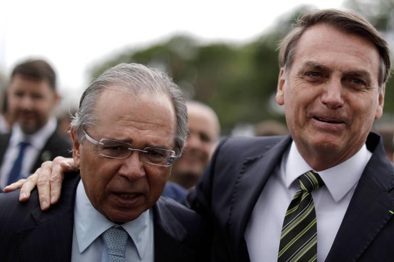 Na direita, Paulo Guedes; à esquerda, Jair Bolsonaro repousa a mão no ombro esquerdo do ministro