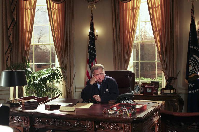 """O ator Martin Sheen no papel de presidente Bartlet em """"The West Wing"""", um drama que trata de Washington como uma capital dirigida por boas pessoas. Ele está sentado na mesa da sala oval."""