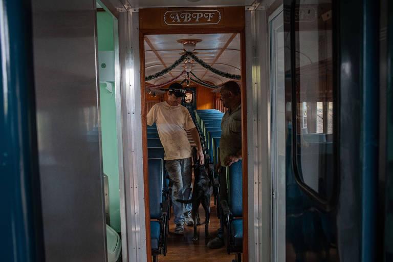 Ronaldo Antonio Fernando (esq.) e Antonio Edson Laurindo dos Santos dentro de trem na associação