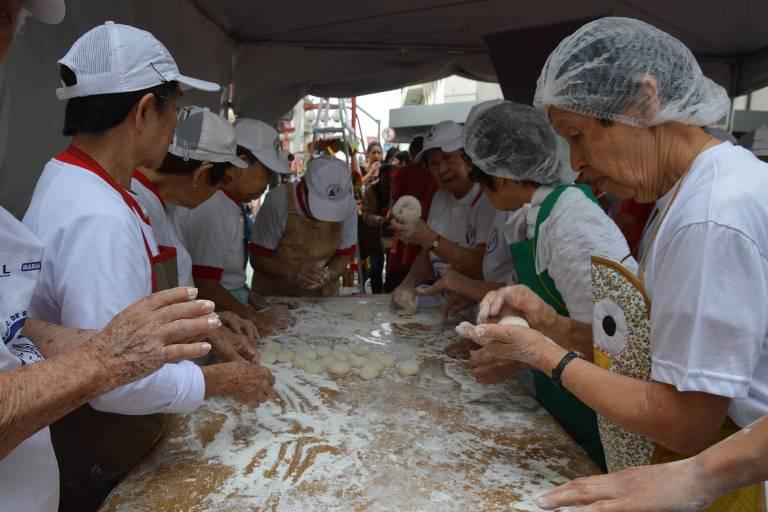 Voluntários preparam o moti numa edição de Réveillon na praça da Liberdade, em SP