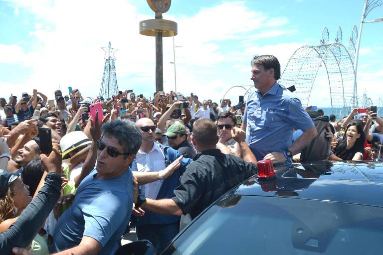 Bolsonaro aparece cercado por pessoas, que filmam e fotografam com os celulares