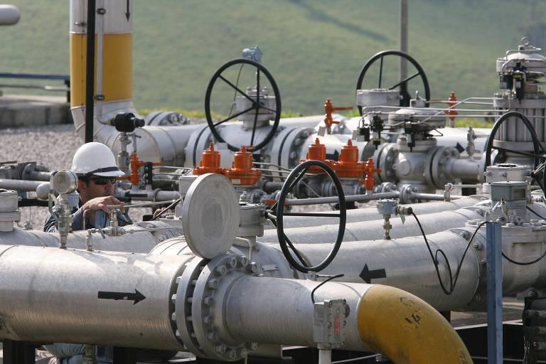 Um técnico da Transportadora Brasileira Gasoduto Bolívia-Brasil (TBG) faz manutenção em linhas de alta pressão de ás natural. Ele está agachado entre os canos, vestindo um capacete branco e óculos de sol.